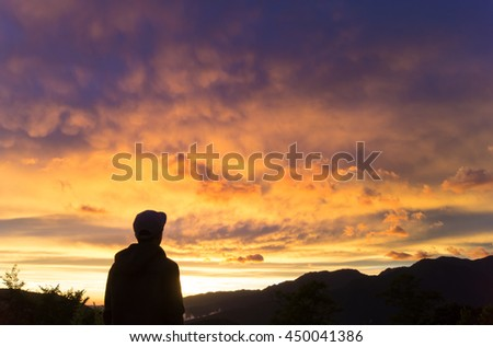 the silhouette of man looking forward with mountains under colorful sunset sky