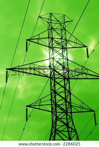 The silhouette of power lines agains a green sky. - stock photo