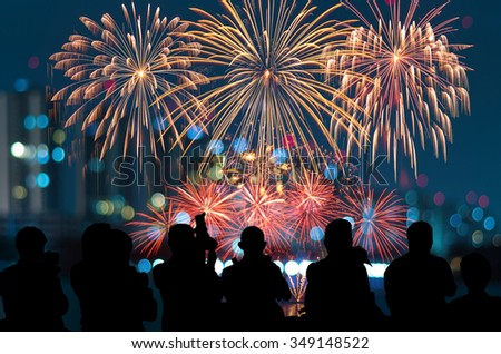 The silhouette of reporter photograph the Fantastic festive new years colorful fireworks on cityscape blurred photo bokeh,project success, holiday concept