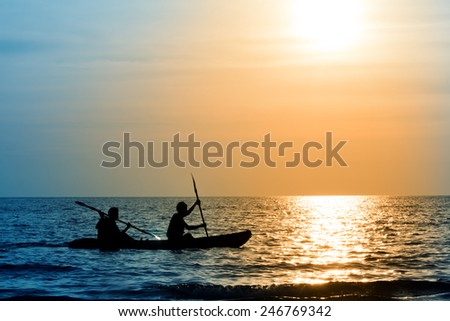 The silhouette of rowing boat with 2 rowers on the background of the sunset - stock photo
