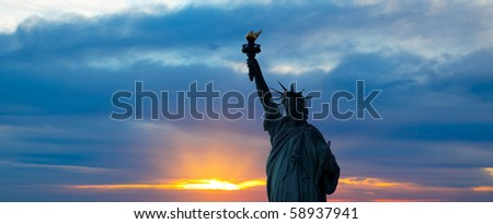 The silhouette of Statue of Liberty under sunrise background - stock photo