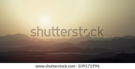 the silhouette of the mountains at sunset
