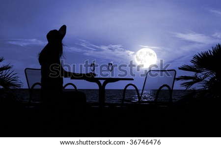 The silhouette of the woman sits at a table in cafe on a moon night