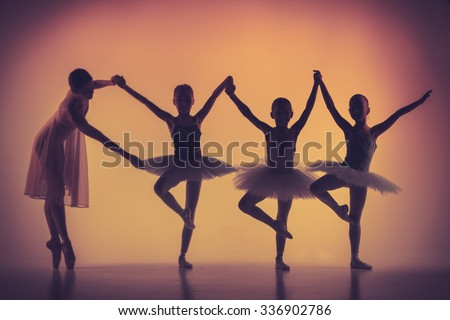 The silhouettes of little ballerinas with personal ballet teacher in dance studio posing on a orange background - stock photo