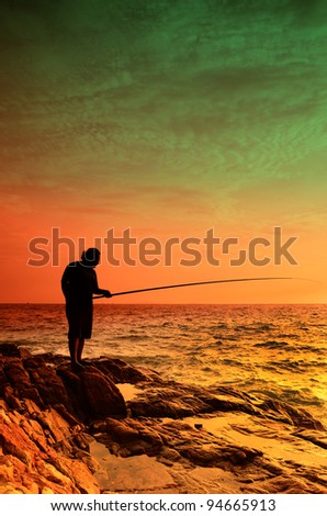 the silhoutte of people standing on the rocks while fishing - stock photo