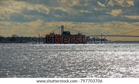 The silver water of the East River, in the background the orange Staten Island Ferry and Manhattan Bridge under a cloudy sky in New York, United States.