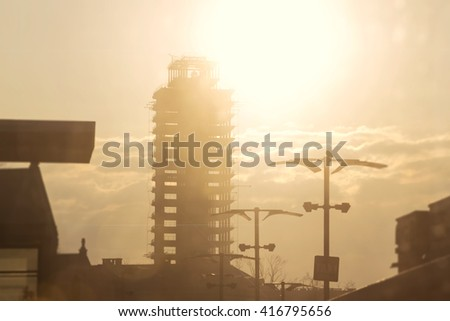The skeleton of the building under construction. The city in the morning