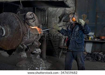 The skilled worker aluminum melts in an electric furnace for molding parts