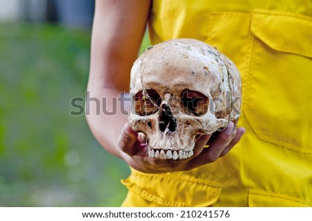 The skull in the hands of monk - stock photo