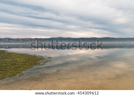 The sky at dusk reflecting clouds and pastel colors in the water of a lagoon in Kynsna, South Africa - stock photo