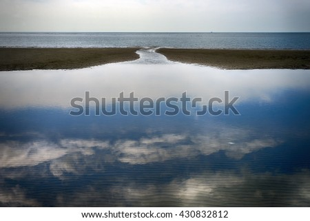 The sky reflecting in the sea on the beach by the North Sea, Denmark. - stock photo