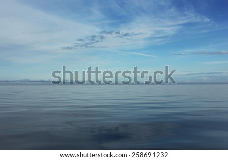 The sky with the clouds  and the calm water at the beginning of the evening, both bright and blue. - stock photo