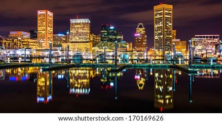 The skyline and docks reflecting in the water at night, in the Inner Harbor of Baltimore, Maryland. - stock photo