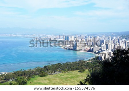 The skyline of bustling Honolulu with Waikiki and the Pacific ocean in the foreground as seen from the top of Diamond Crater Mountain on a clear morning. - stock photo