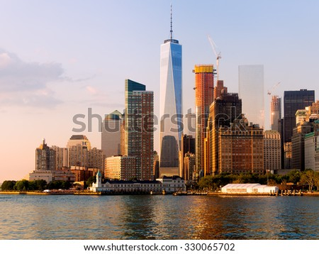 The skyline of downtown Manhattan at sunset with reflections on the sea