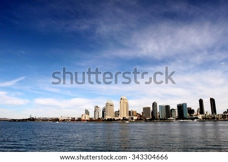 The skyline of San Diego with water in the front and cloudy blue sky in the background. - stock photo