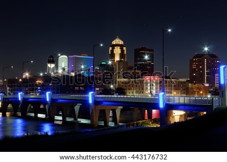 The skyline of the city of Des Moines lights up after dark. This night the Financial Center was lit up in rainbow colors in tribute of the Orlando mass shooting. - stock photo