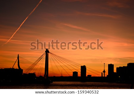 The skyline of the city of Rotterdam in the Netherlands over the water of the river Maas during sunset. - stock photo