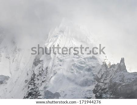 The slope of the Nuptse (7864 m) into mist (view from Kala Patthar) - Everest region, Nepal, Himalayas - stock photo