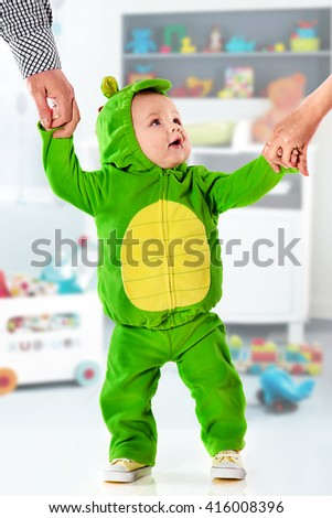 the small boy in a green suit of a dragon holds parents by hands - stock photo