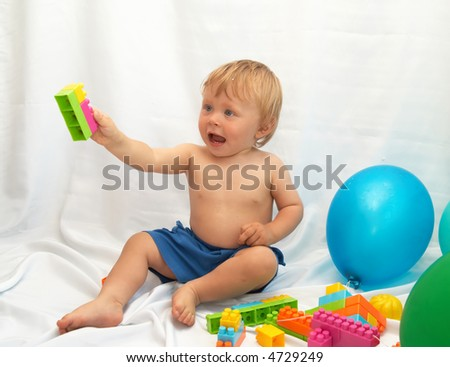The small boy plays toys on a white background