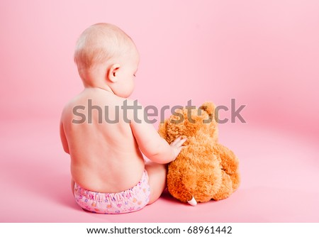 The small child with a bear cub on a pink background - stock photo