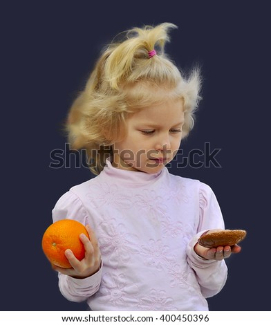 The small  girl holds an orange and biscuits.