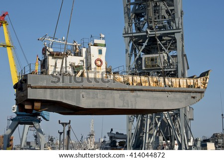 The  small  marine  vessel  rearrange   powerful  floating  crane  for  repair  of  the  ship's  hull