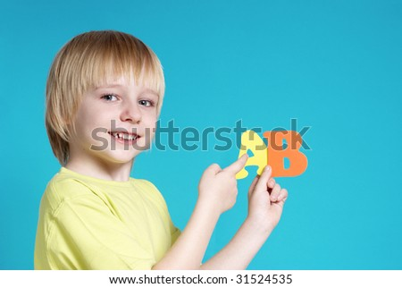 The small schoolboy with letters on a blue background - stock photo