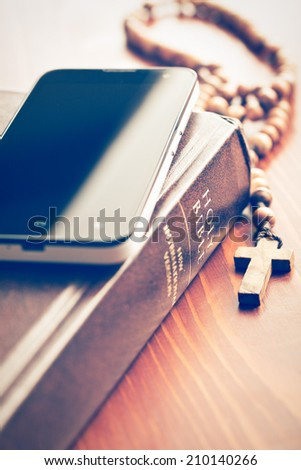 the smartphone with holy bible and rosary - stock photo