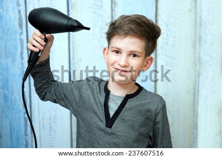 The smile boy with black blow dryer against wooden wall - stock photo