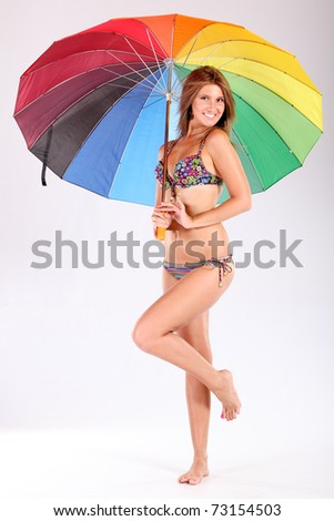 The smile girl in bikini with a multi-coloured umbrella - stock photo