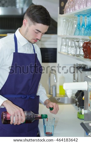 the smiling barman at work he prepares cordials