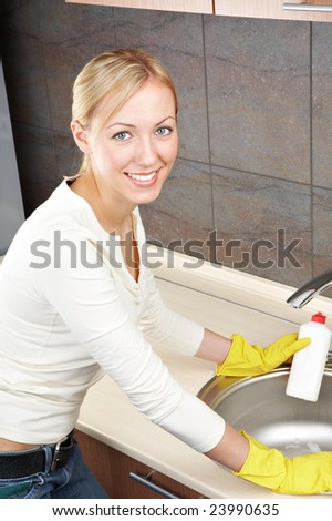 The smiling blonde is engaged in kitchen cleaning - stock photo