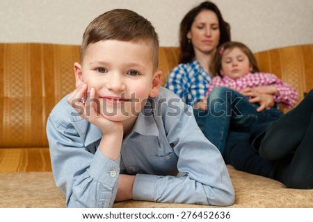 The smiling boy having leaned the elbows on a hand lies on a sofa. His mother and his sister on a background.