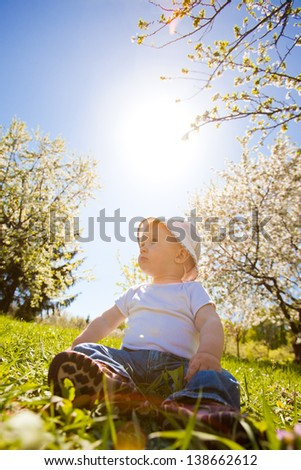 The smiling boy sits on a grass under sun beams - stock photo