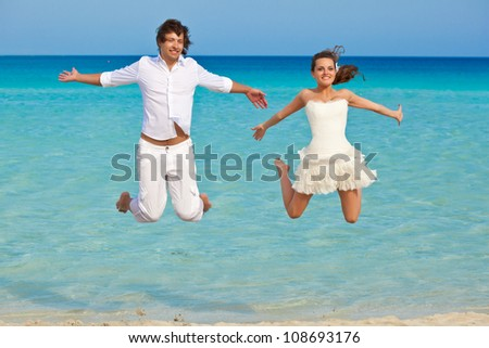 The smiling couple is jumping in the sea - stock photo