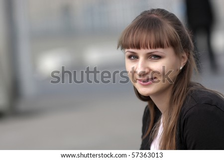 The smiling girl poses at a street - stock photo