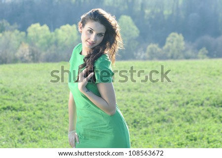 the smiling girl with green dress touches her hair in a natural - stock photo