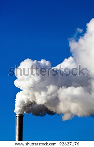 the smoking chimneys of a factory against a blue sky. white smoke rises from chimneys on - stock photo