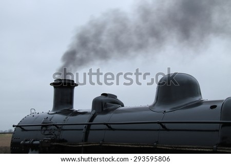 The Smoking Funnel of a Vintage Steam Engine Train. - stock photo