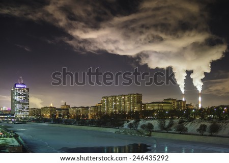 The smoking pipes and the river. Night cityscape. - stock photo