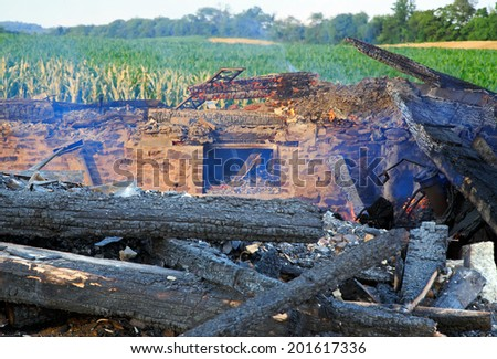 The smoldering remains of a rural home which was completely destroyed by fire. - stock photo