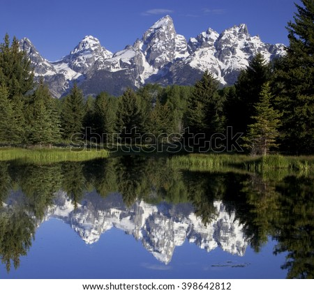 The snow-capped peaks of the Grand Tetons reflect off a beaver pond at Schwabachers Landing