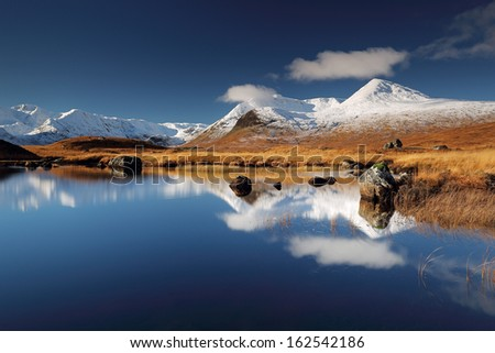 The snow covered Blackmount mountain range reflecting on Loch Ba near Glencoe, Scotland. - stock photo