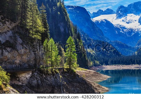 The snow-covered peaks in the Alps with a beautiful green mountain slopes. In the bottom of the lake. - stock photo