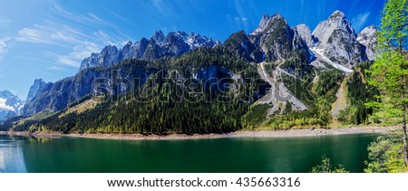 The snow-covered peaks in the Alps with a beautiful green mountain slopes. In the bottom of the lake.