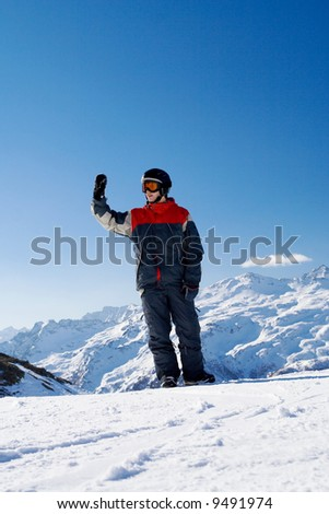 The snowboarder on a background of mountains and the blue sky