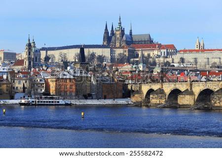 The snowy Prague gothic Castle with the Charles Bridge, Czech Republic - stock photo