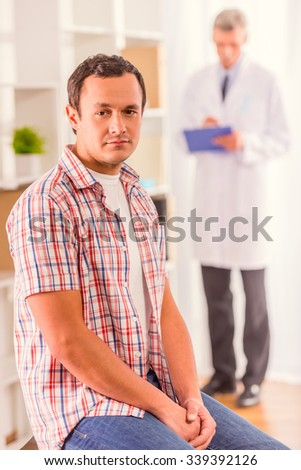The social problem of male diseases. Portrait of doctor and patient man with a blue ribbon sitting in the office - stock photo